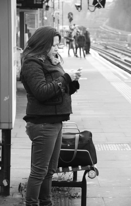 Woman checking mobile phone, Finchley Central Tube Station, London N3, 16th Feb 2015. people, london, monochrome, tubestation. buy photo