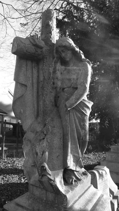 Woman with cross grave marker, churchyard Hendon London NW4, 29th December 2014. london, monochrome, cemetery, moody, gothic, northlondon. buy photo