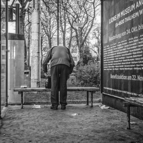 Man searching something in his bag. man, square, streetphotography, streetlife, squareformat, streetshot, manfrombehind. buy photo